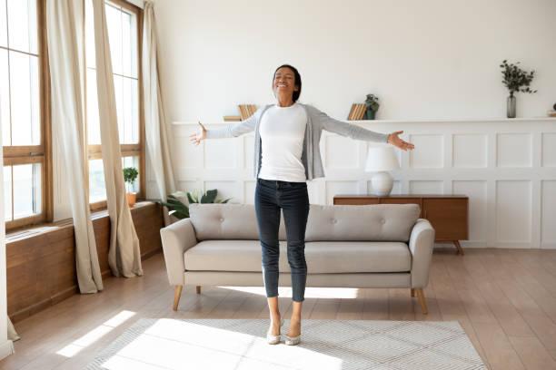 glad afroamerikansk kvinna dansar hemma i vardagsrummet - återhämtning bildbanksfoton och bilder