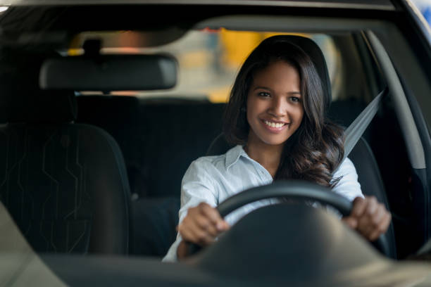 happy african american woman driving a car - driver stock photos and pictures
