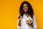 istock Happy african american woman eating healthy salad 1178132505