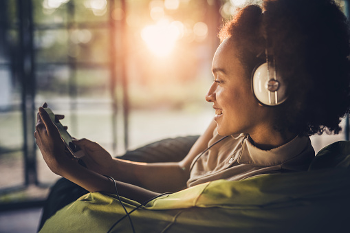 Profile view of happy black woman relaxing in bean bag and surfing the Internet on her smart phone while listening music on headphones.