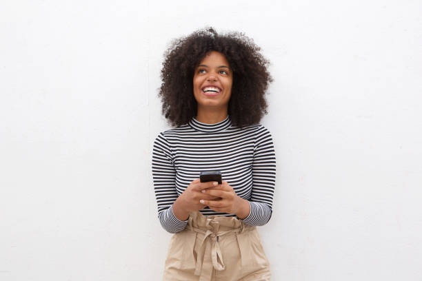Happy african american woman holding smart phone Portrait of happy african american woman holding smart phone afro caribbean ethnicity stock pictures, royalty-free photos & images