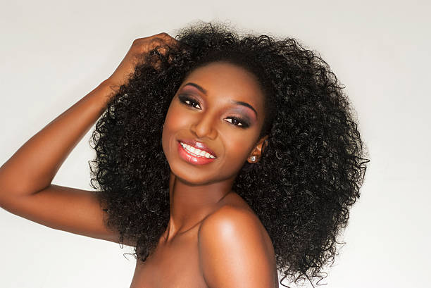 Happy african american woman loving her curly hair stock photo