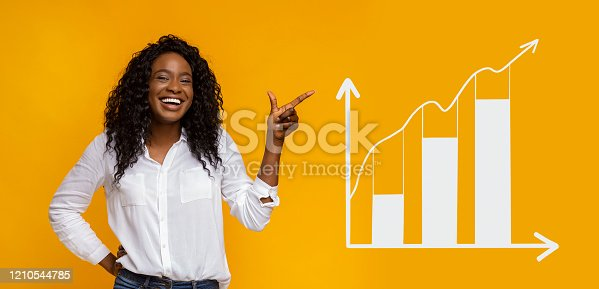 Smiling African American woman pointing aside at business graph