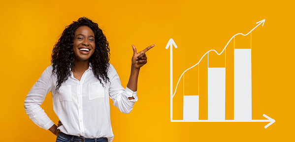 istock Happy African American woman pointing aside at business graph 1210544785