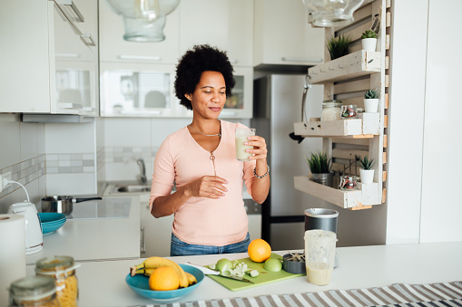 Cheerful African American woman having a healthy breakfast at home, making a shake out of different kinds of fruits and smiling