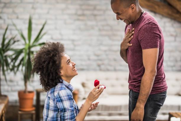 feliz mujer afroamericana propone a su novio en casa. - prometido fotografías e imágenes de stock