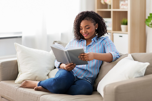 leisure, literature and people concept - smiling african american woman reading book at home