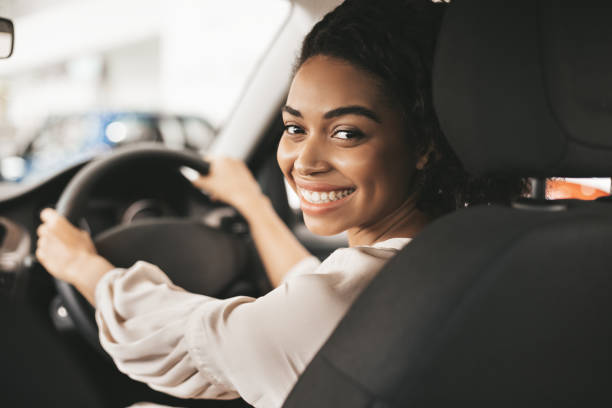 Happy African American Woman Sitting In Auto In Dealership Center stock photo