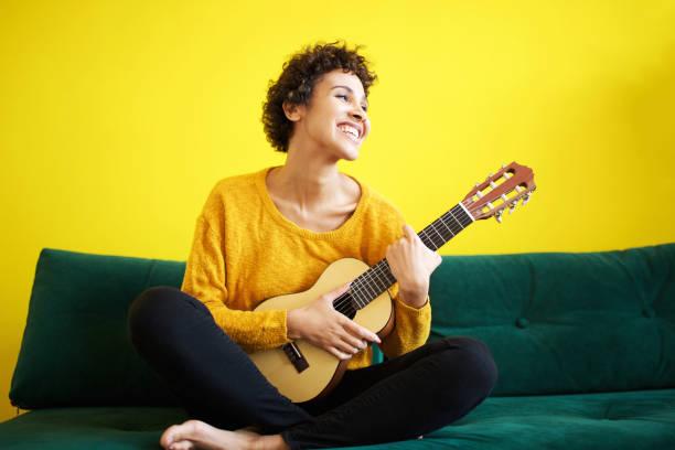 glückliche afrikanische amerikanische Frau sitzt auf Sofa mit Gitarre – Foto