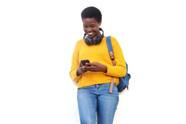 Glückliche afrikanische Amerikanerin lächelt vor weißem Hintergrund mit Smartphone und Tasche – Foto