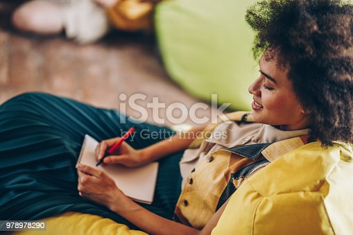Smiling African American student taking notes while trying to remember the things she has learned for her exams.