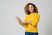 Attractive young African American woman using her high-tech electronic device to help her in education isolated on light gray background