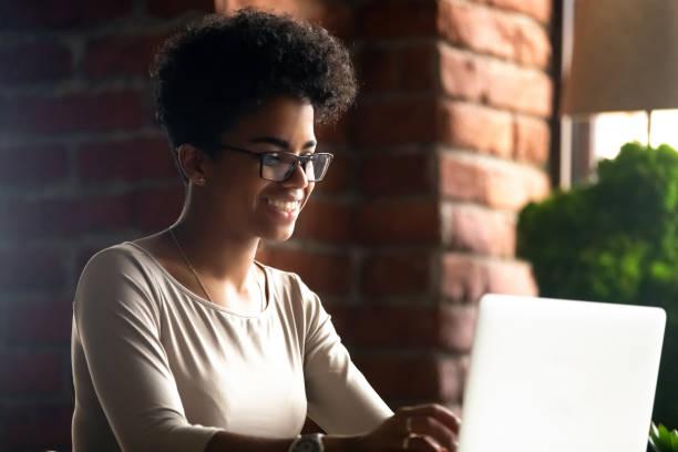 glückliche afroamerikanische frau mit laptop, mit freunden chatten - nachrichten video stock-fotos und bilder