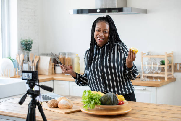 happy african american woman vlogger broadcasting cooking live video at home - side hustle stock pictures, royalty-free photos & images