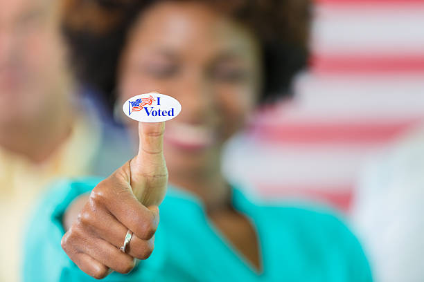 happy african american woman with an i voted sticker - vote photos et images de collection