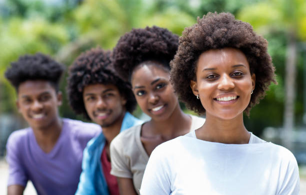 Happy african american woman with group of young adults in line Happy african american woman with group of young adults in line outdoor in city in summer côte d'ivoire stock pictures, royalty-free photos & images