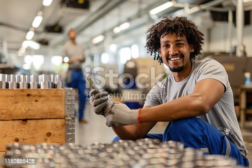 Happy black steelworker inspecting finished products in a factory and looking at camera.
