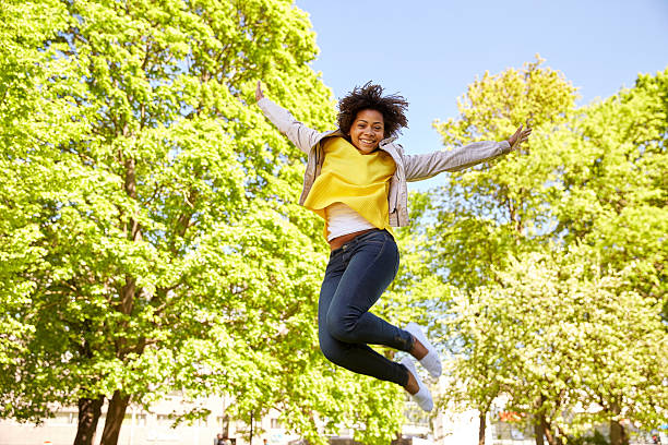 happy african american young woman in summer park - african youth jumping for joy stock photos and pictures