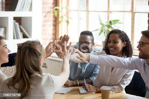 Happy african and caucasian diverse people give high five together celebrate great teamwork result motivated by team spirit, business success victory, unity concept, good relations and teambuilding