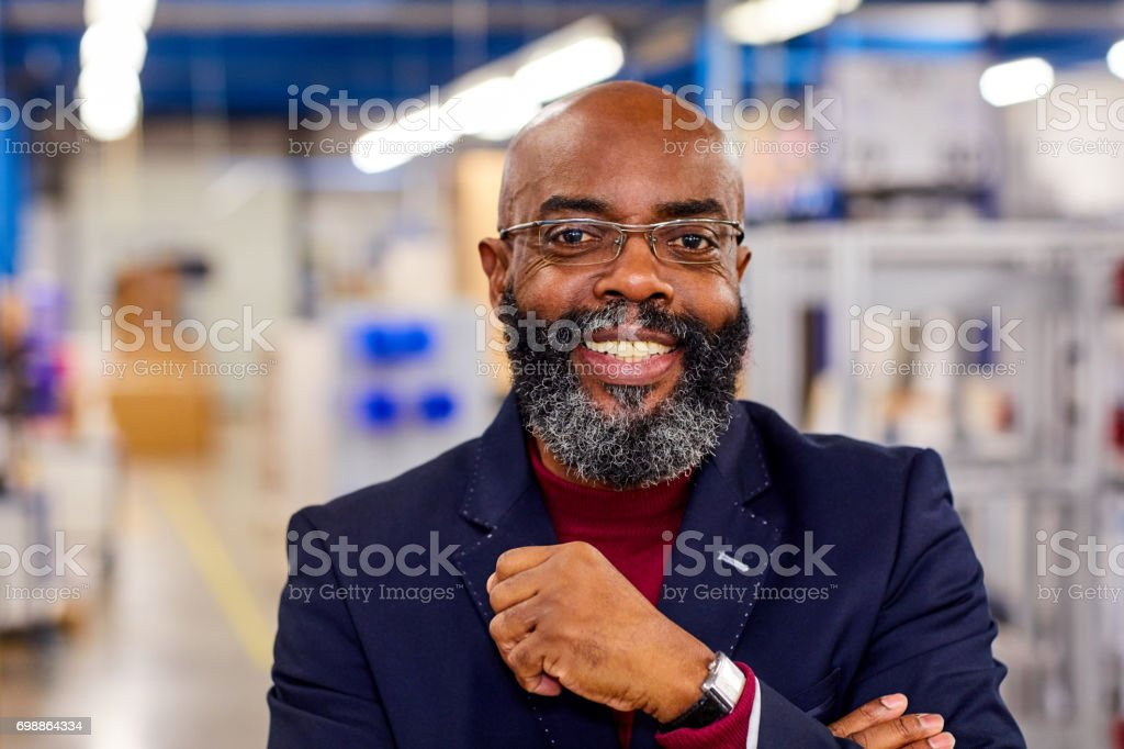 Happy african businessman standing in factory stock photo