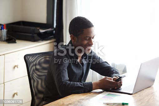 istock happy african businessman using mobile phone at office 1036091726