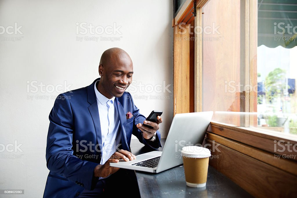 Happy african businessman using phone at cafe stock photo