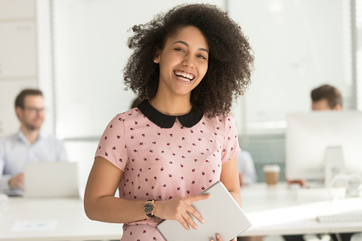 Happy african businesswoman holding digital tablet looking at camera