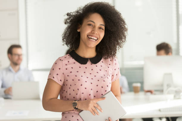 Happy african businesswoman holding digital tablet looking at camera Happy confident african american business woman employee holding digital tablet looking at camera standing in office, smiling millennial mixed race female intern manager young professional portrait apprentice stock pictures, royalty-free photos & images