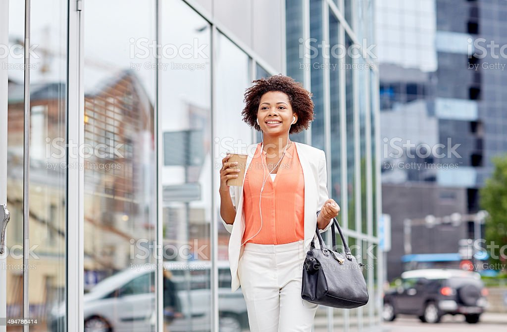 happy african businesswoman with coffee in city stock photo