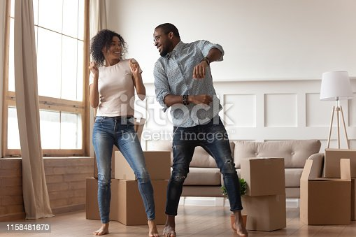 Happy carefree african couple first time home buyers renters owners dancing laughing in living room with boxes together, funny black tenants having fun enjoy relocation in new house on moving day