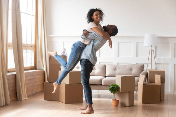 happy african couple first time home buyers celebrate moving day - future hug imagens e fotografias de stock