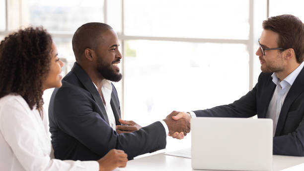 Happy african couple shake hand of insurer buy insurance services stock photo