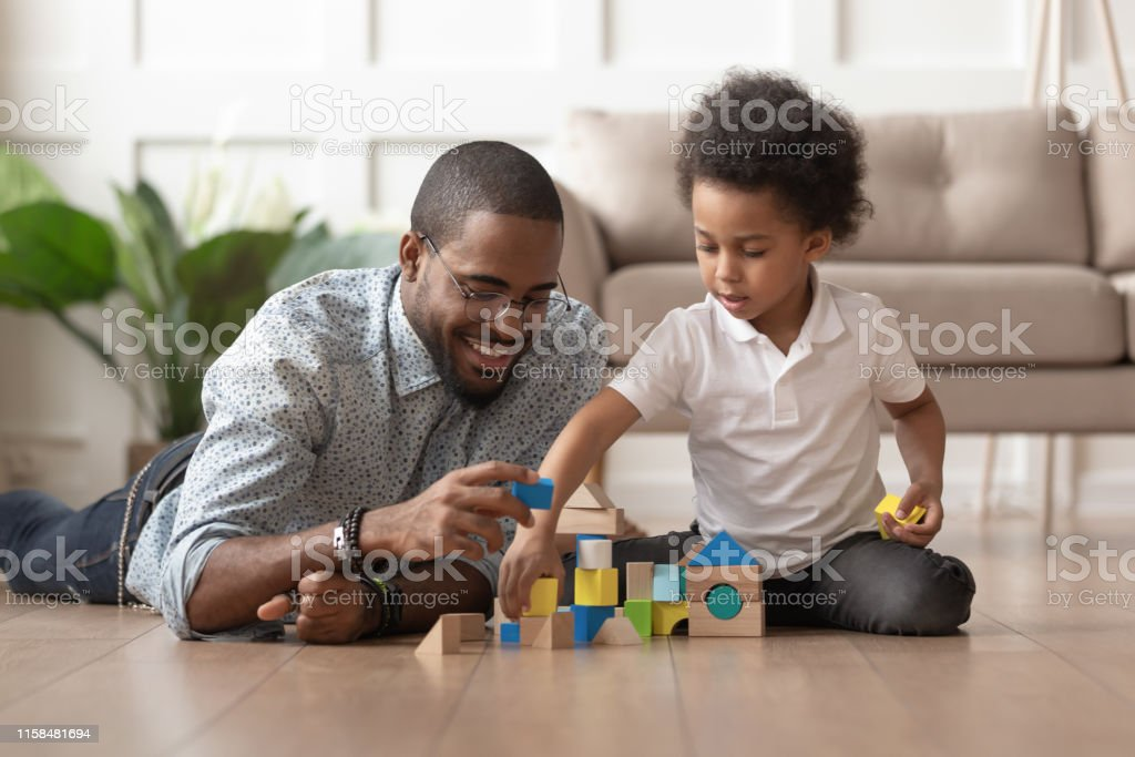 Happy african dad and child son building constructor from blocks Caring young single black father help cute kid son play on warm floor together, happy african family dad and little child boy having fun building constructor tower from colorful wooden blocks Adult Stock Photo