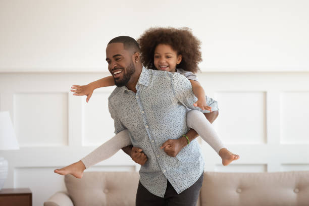 Happy african dad piggybacking little daughter having fun at home Happy african american dad piggybacking little funny daughter having fun at home, laughing black father carrying cute small kid on back playing together bonding enjoying active leisure in living room piggyback stock pictures, royalty-free photos & images