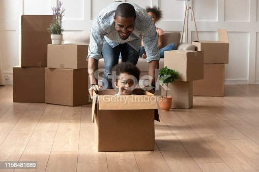istock Happy african dad playing with little son riding in box 1158481689