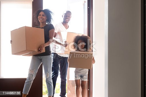 istock Happy african family with little daughter arrive at new home 1144680135