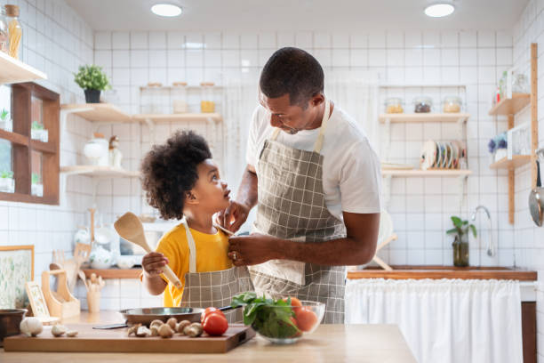 Happy African father and son dress up together before cooking in the white kitchen. Eye Contact, Relationship, Talking, Warm Family. stock photo