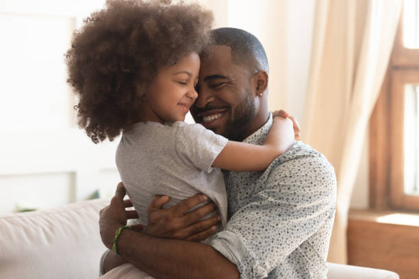 Happy african father holding embracing cute little child daughter Sweet moments of fatherhood concept, happy african father hold embrace cute little child daughter, smiling black family mixed race daddy and small kid hugging cuddling enjoying time together at home father stock pictures, royalty-free photos & images
