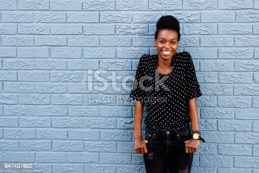 istock Happy african female standing against gray brick wall 647437602