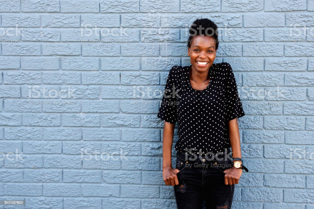 Happy african female standing against gray brick wall - foto de stock