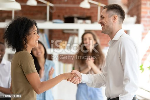 istock Happy african female worker getting promoted handshaking caucasian boss 1139791183