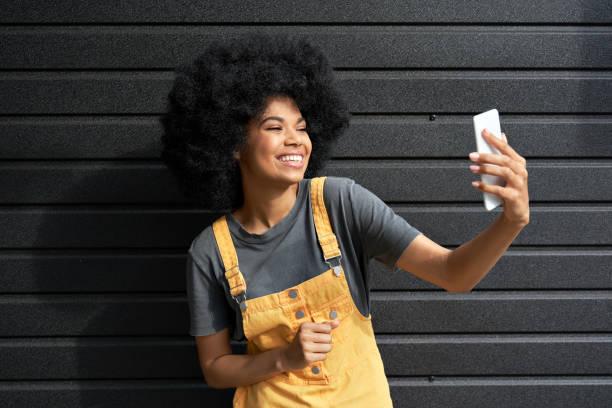 スマートフォンの撮影vlogやビデオ通話を保持している幸せなアフリカの女の子ブロガー。 - gen z ストックフォトと画像