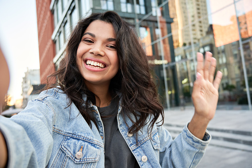 Happy Afro American hipster teen girl blogger influencer recording vlog holding looking at camera. Black woman travel vlogger shooting blog, streaming, video calling on urban city street, headshot.