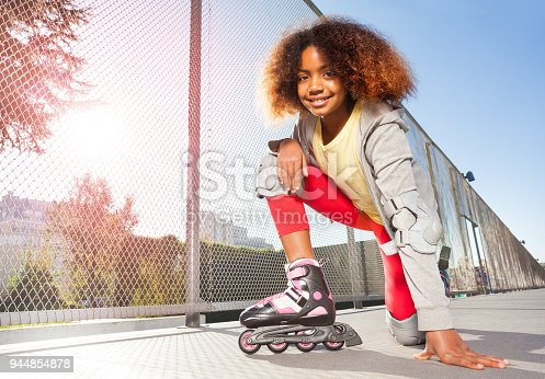 Happy African girl wearing inline slates and protective gear, posing on floor at skate park