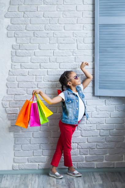 glücklich afrikanisches mädchen mit einkaufstüten - laminat günstig stock-fotos und bilder