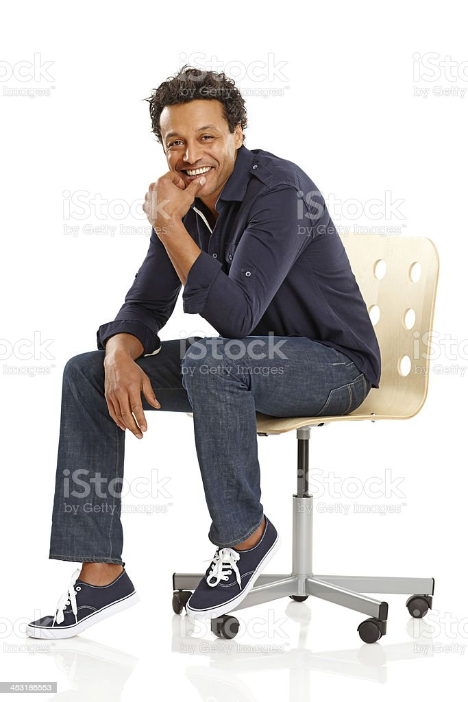 Happy African guy sitting on chair looking at you stock photo