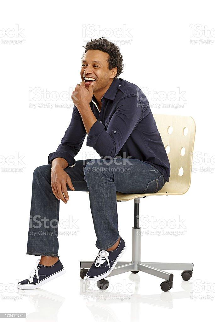Glücklicher afroamerikanischer Mann sitzt auf Stuhl Wegsehen – Foto