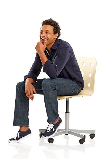 Heureux homme africain assis sur la chaise à la recherche de l