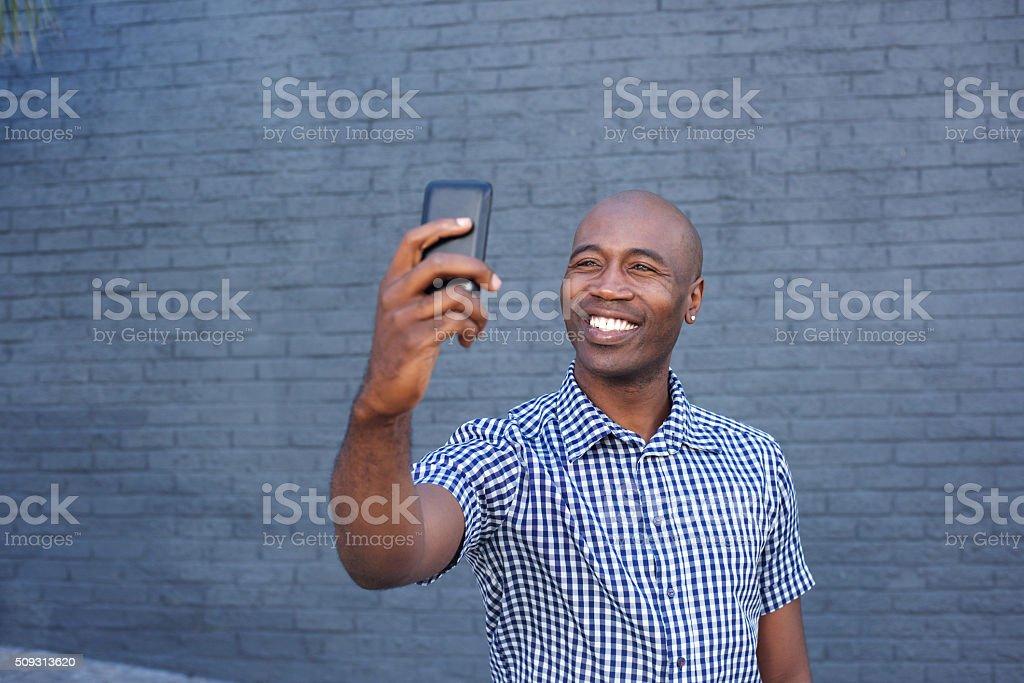 Heureux afro homme prenant un selfie avec son téléphone portable - Photo