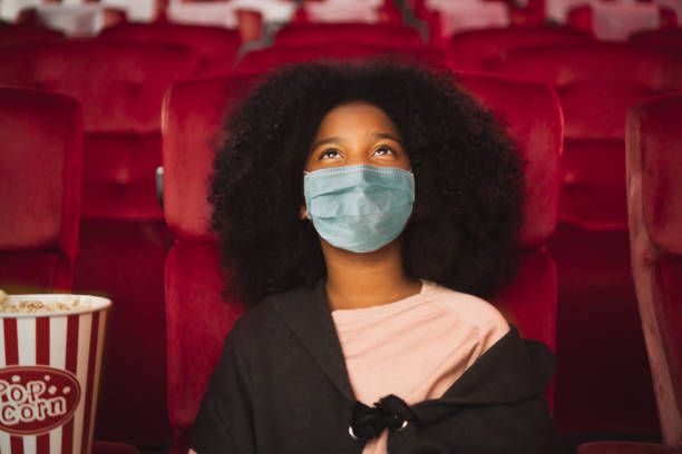 Happy african kid wearing protective face mask and watching movie in theater/theatre cinema protect infection from coronavirus covid-19, social distancing in theatre concept stock photo
